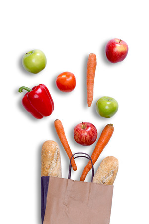 Fresh balanced grocery shopping concept with a brown paper carrier bag with fresh crusty baguette, carrots, apples, sweet bell pepper and tomato arranged on a white surface, view from above