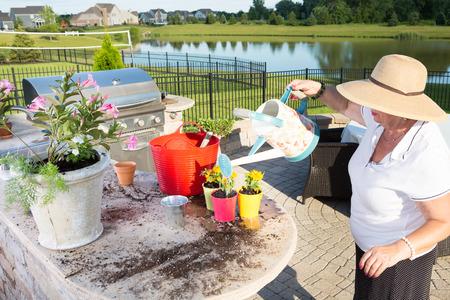 Sommerküche Waschbecken : Ltere dame befüllen einer gießkanne in einem waschbecken in einem