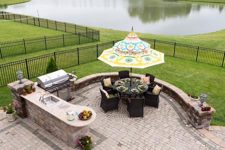 Espacio de vida al aire libre en un patio de ladrillo con vistas a un lago tranquilo y verde césped vallada con una mesa bajo una sombrilla o paraguas puso listo para la cena, vista de ángulo alto
