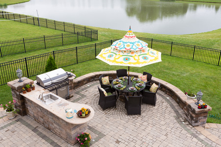 Outdoor living space on a brick patio overlooking a tranquil lake and fenced green lawn with a table under a sunshade or umbrella laid ready for dinner, high angle view