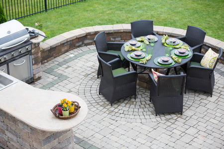 lifestyle outdoors: Elegant outdoor living space on a paved brick patio with a summer kitchen and barbecue and a table laid with formal place settings for dinner, high angle view Stock Photo