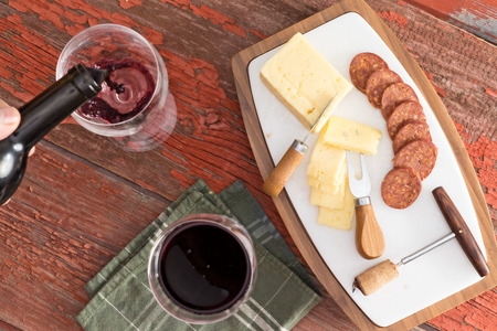 table top: Aerial Shot of Sliced Cheese and Sausage on Top of a Cutting Board, with Glasses of Red Wine, Served on Top of a Wooden Table. Stock Photo