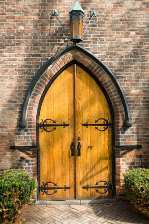 Old arched wooden double door in a face brick building facade in Gothic style with a herringbone patterned paved path and neat hedges lining the approach