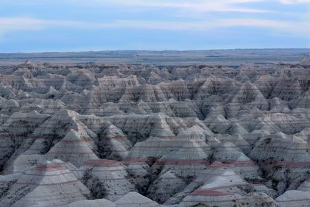 Landscape view of the Badlands National Park in South Dakota showing the topography of the eroded rock forming buttes and pinnacles with exposed rock strata in layers