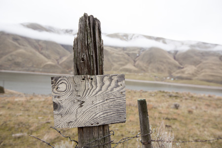Old rustic blank wooden signpost with an interesting wood grain pattern on an old fence pole with the Snake River, Idaho in the background