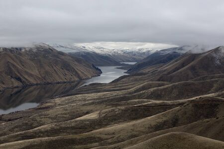 snake: View along the Snake River Canyon between Idaho and Oregon in the Magic Valley Region in winter with snow capped mountains and cloud cover Stock Photo