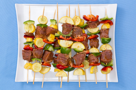Tasty spicy marinated meat and vegetable kebabs displayed on a platter on their skewers ready for the summer barbecue, overhead view on a blue background 版權商用圖片