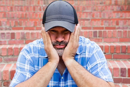 goatee: Boredom - the enemy of human happiness in a conceptual image of a middle-aged man with a goatee sitting resting his chin in his hands with a glum expression staring at the camera against a brick wall