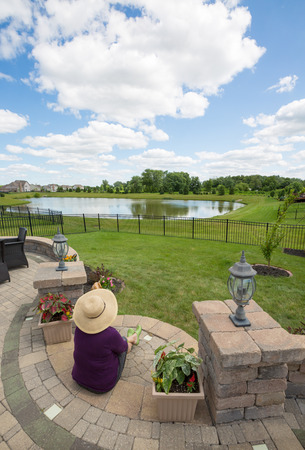 unwinding: View from above of a woman in a straw sunhat sitting on her patio enjoying the view over green fields and a lake under a cloudy blue sky in spring sunshine