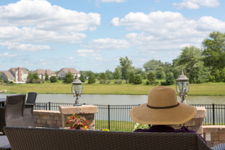 back yard pond: Woman in a sunhat sitting on a patio bench overlooking her garden and a tranquil lake enjoying the summer weather and pretty fluffy white clouds in a blue sky