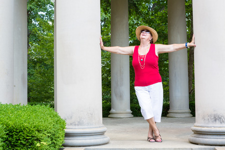 head tilted: Happy Feel Good trendy modern grandma leaning with outstretched arms between two columns celebrating the sunshine and nature with her head tilted to the sun