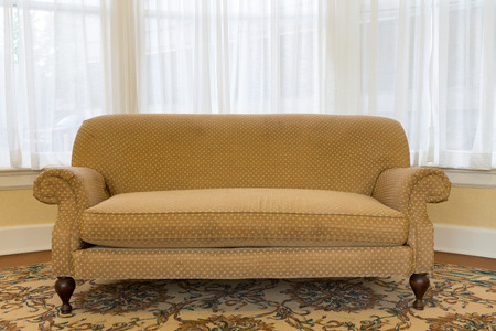 Close up Empty Elegant Brown Couch Furniture at the Living Area with White Curtains to Glass Windows on the Background. Stock Photo