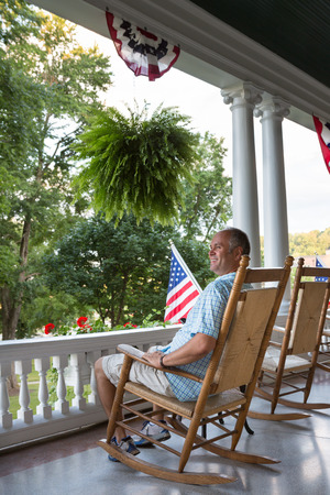 Happy Middle Age Man Sitting on Wooden Rocking Chair at the Terrace and Viewing the Relaxing Nature While Enjoying the 4th Day of July in USA.