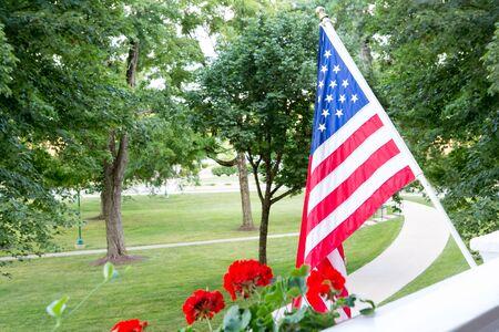 アメリカ星条旗の旗はバルコニーまたは愛国心が強いジェスチャーまたは 7 月 4 日を祝うために木が付いている公園を一望するパティオからと独立記念日
