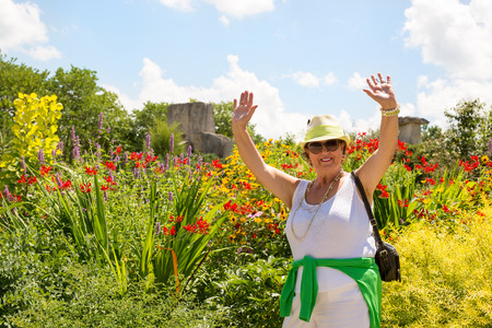 Trendy joyful Grandma outdoors in her garden laughing and waving her hands in the air in front of a bed of colorful summer flowers