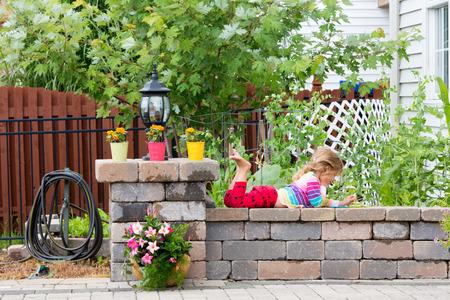 따뜻한 햇살을 즐기는 공기에 그녀의 발을 낮은 정원 벽에 밝은 화려한 옷 거짓말을 연주 귀여운 소녀 스톡 콘텐츠