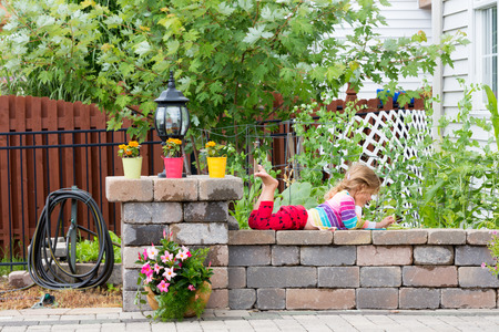 Cute little girl in bright colorful clothing lying playing on a low garden wall with her feet in the air enjoying the warm sunshine