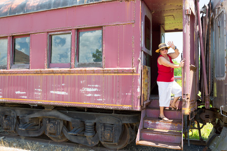 Elderly woman in trendy summer clothing standing waving at the camera from the steps of a vintage train carriage in a conceptual image of travel and vacations photo