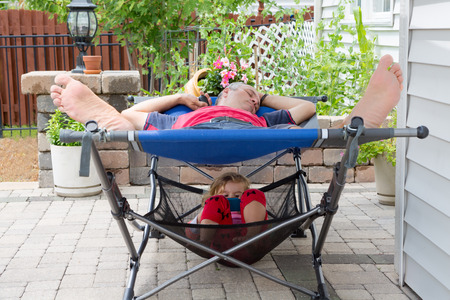 recliner: Father and daughter relaxing together on the patio both lying on a two-tiered recliner chair with the little girl curled up snugly below, view perspective from the feet Stock Photo