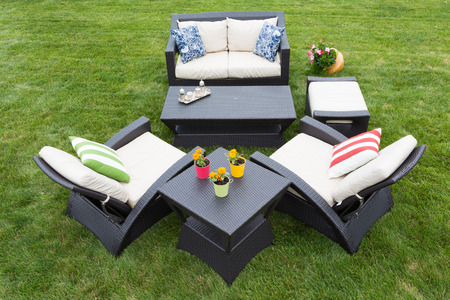 stylish armchairs and a two seater settee arranged on a neat manicured green lawn with tables decorated with potted plants Stockfoto