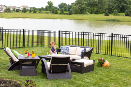 furniture: Cute little blond girl standing amongst comfortable modern design garden furniture with armchairs and tables arranged on a neat green lawn overlooking a tranquil pond and wrought iron railing
