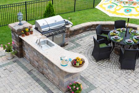 ladrillo: elegante cocina, barbacoa de gas y mesa de comedor conjunto al aire libre para entretener a los invitados con ajustes de lugar formales y flores en un patio pavimentado Foto de archivo