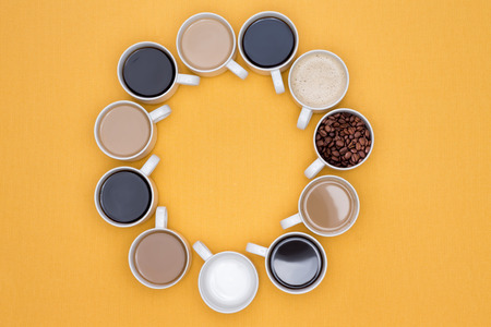 brew house: Cups of Hot Coffee in Different Flavors Arranged in Circle on a Yellow Background