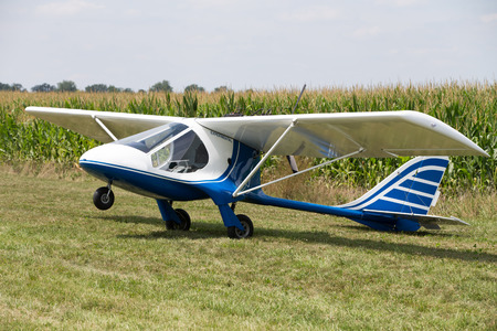 fixed wing aircraft: Small little single engine microlight experimental plane sitting on a field Stock Photo