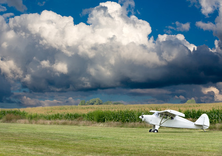 fixed wing aircraft: Small white microlight plane ready for take off on a rural field with corn fields alongside under a dramatic cumulus cloud formation
