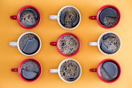 alternating: Mugs of black coffee in alternating red and white colors in an order placed on an orange background