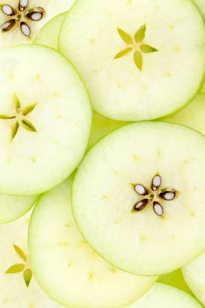 Conceptual background pattern and texture of sliced fresh green organic apples with the pip detail forming an attractive star to the center of each slice, overhead view photo