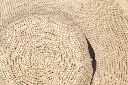 Background texture of a straw sunhat viewed from above showing the pattern of the weave on the crown and brim photo
