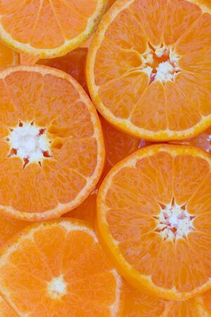 overlaying: Conceptual background texture and pattern of slices of juicy succulent clementine overlaying each other in a full frame food background with central white coloration to the fruit