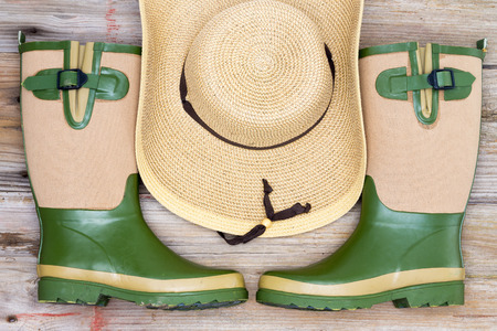 Garden fashion accessories with stylish rubber gumboots and a wide brimmed straw hat in a symmetrical arrangement, view from above Reklamní fotografie