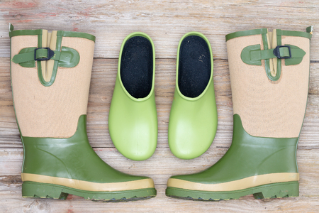 clogs: Stylish footwear for the garden with green rubber clogs and elegant matching green and beige gumboots in a symmetrical arrangement on a rustic wood background
