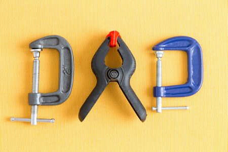 tool kit: Assorted clamps from Dads tool kit with adjustable grey and blue G-clamps and a spring loaded plastic A-clamp Stock Photo