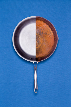 new age: New coated non-stick and old rusted frying pan combined into one halved unit for comparison of age and condition in a conceptual overhead view on a blue background