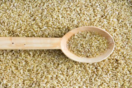 centered: Overhead background texture of dried crushed or cracked wheat with a spoonful in a wooden spoon centered through the frame