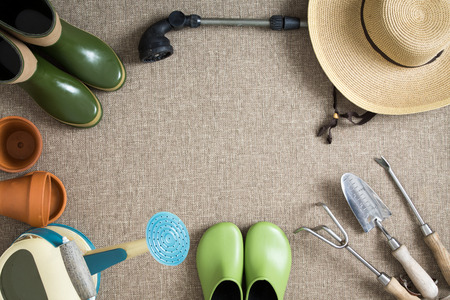 the hand tools: Border or frame of gardening tools on a neutral beige textile background with garden shoes and boots, sunhat, watering can, hand tools and flowerpots, with central copyspace, view from above Stock Photo