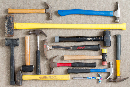 Large selection of different hammers and mallets arranged on a neutral beige background viewed from above in a DIY, renovation, maintenance,and construction concept photo
