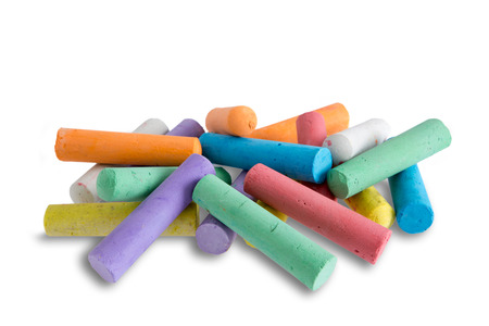 Collection of bright colorful chalk crayons piled in a random heap ready for young elementary school children to use for creative drawing and entertainment, on white photo