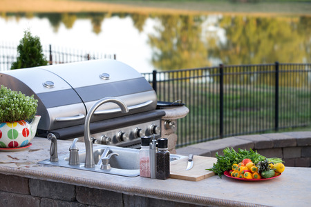 Preparing a healthy summer meal in an outdoor kitchen with gas barbecue and sink on a brick patio overlooking a tranquil lake with tree reflections Stockfoto