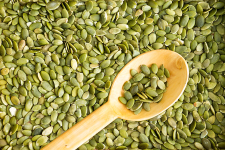 Full frame background texture of fresh cleaned green pumpkin seeds with a rustic wooden spoon arranged diagonally on the surface for use in salads or as a tasty snack Archivio Fotografico