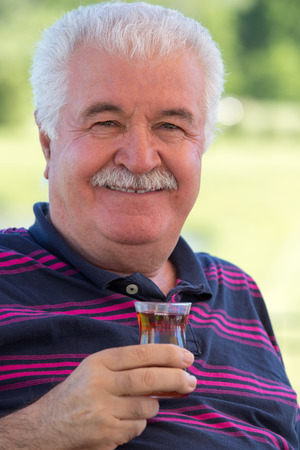 distinguished: Smiling distinguished attractive senior man enjoying a glass of tea outdoors on a sunny summer afternoon smiling at the camera, focus to the glass Stock Photo