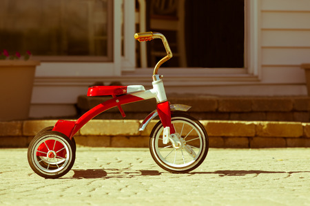 cherished: Childs rusted favorite cherished red tricycle standing ready and waiting for its owner to arrive on paving outside a house Stock Photo