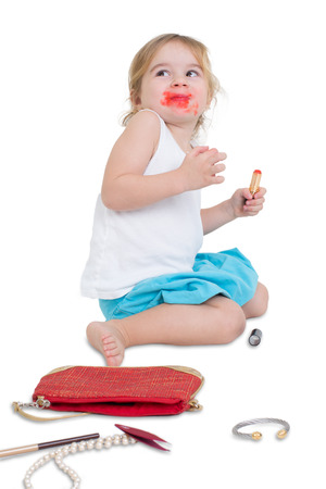 a righteous person: I didnt do it fun concept with a naughty little girl with her mouth smeared with lipstick surrounded by her mothers scattered cosmetics looking upwards with a guilty look, isolated on white
