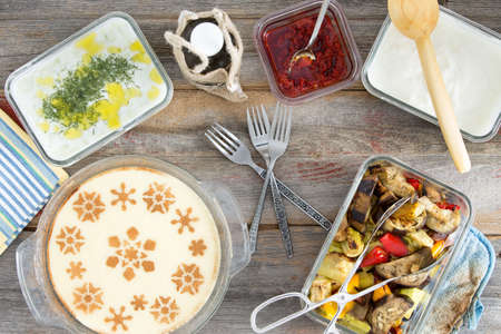 Delicious picnic lunch with grilled vegetables, tzatiki, yogurt with dill, pepper paste and a decorative milky semolina dessert , overhead view on a wooden table photo