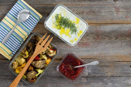 Healthy meal of roasted or grilled assorted vegetables including sweet pepper, eggplant and zucchini served with tzatziki or Turkish cacik with yogurt and dill and a pepper paste on an old wood table photo