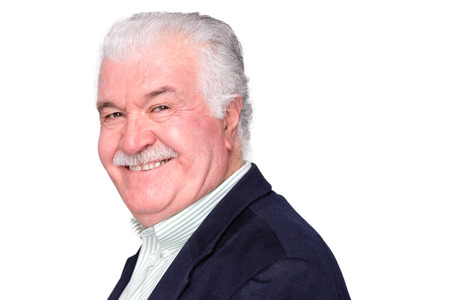 Charismatic happy attractive senior man with a lovely warm smile turning to look at the camera with an amused expression, on white Stock Photo