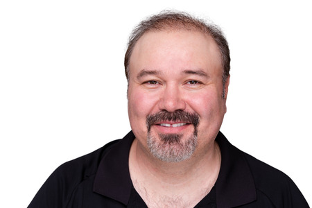 Smiling happy middle-aged man with a goatee beard looking at the camera with a warm friendly smile, isolated on white
